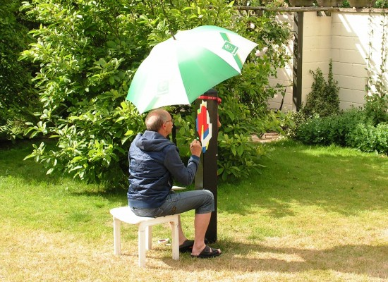 Den gamle golfparaply fra Byggekram skulle beskytte det nymalede mod regn. Men også mod solen der kunne udtørre malingen og skolde kunstnerens isse. Både Kaj Otto og jeg har for mange år tilbage arbejdet sammen for Byggekram kæden. Jeg som kædechef og Kaj Otto som indehaver og kreativ leder af det reklamebureau kæden benyttede.